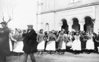 Ο Παπασπύρου - Κόκκινος (με τη τραγιάσκα) στο νταούλι και μπάρμπα - Αδάμης ο Παπασπύρου με τη πίπιζα (δεκαετία '30). Γλέντι μπροστά στον ναό (Από το αρχείο Γ.Δ. Χατζησωτηρίου).