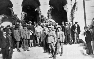 Σπ. Μερκούρης βουλευτής Αττικοβοιωτίας στο μέσον. Στα αριστερά του, (με το μουστάκι, χωρίς σακκάκι) ο Παντοπώλης Πρίφτης. Αριστερά (ασκεπής με τη γραβάτα) δάσκαλος Νάσος Σιδέρης. Δεκαετία 1930. Αρχείο Γ. Δ. Χατζησωτηρίου